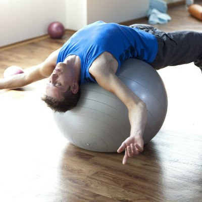 Hombre que se extiende sobre una gran pelota de pilates - Foto: Getty Images