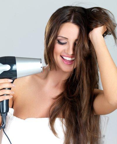 mujer secando su cabello con un secador de pelo - Foto Getty Images