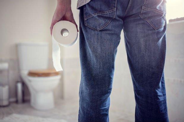 Hombre de espaldas que va al baño con papel higiénico en la mano - Foto: Getty Images